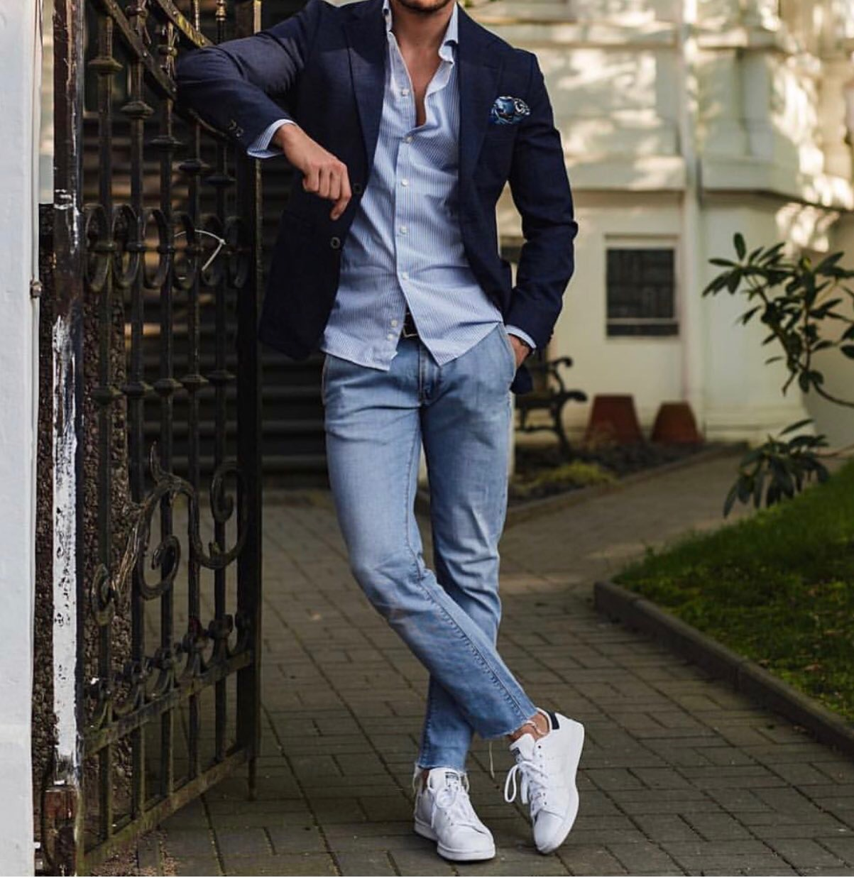 Man in stylish navy blue coat partnered with a light blue button-down shirt, jeans and sneakers